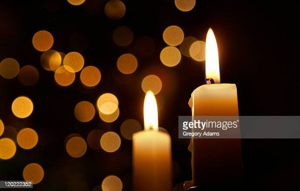 Candles burning in front of out of focus lights