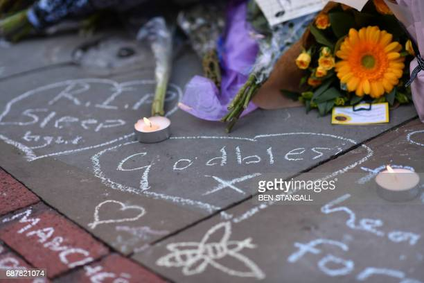TOPSHOT Candles flicker alongside a carpet of flowers and messages at St Ann's Square in Manchester northwest England on May 24 placed in tribute to...