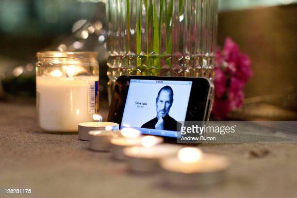 Candles flowers and an iPhone with Steve Jobs photo displayed are seen in remembrance of Steve Jobs founder and former CEO of Apple Inc outside the...
