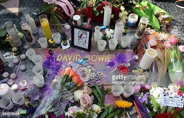 Candles flowers and other momentos are placed on the Hollywood Star of the late British musician David Bowie in Hollywood California on January 11...