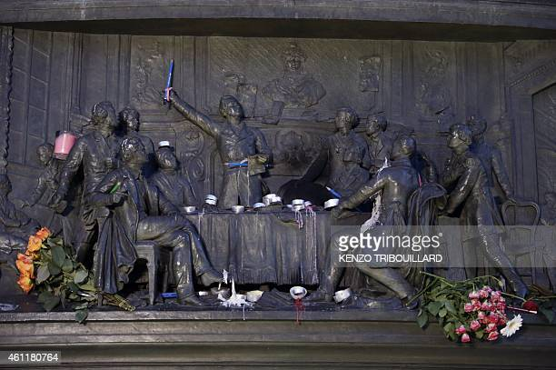 Candles flowers and pens are laid among details of a statue on the Place de Republique in Paris on January 8 as a tribute to the 12 people killed by...