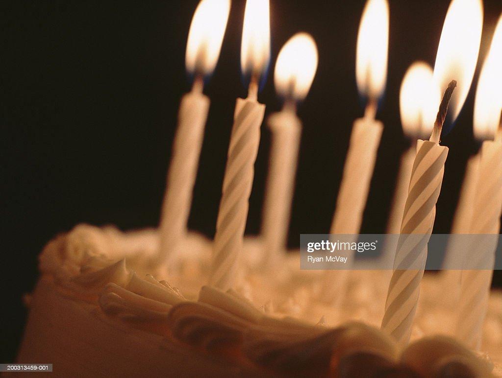 Candles illuminating birthday cake, close-up : Stock Photo