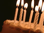 Candles illuminating birthday cake, close-up