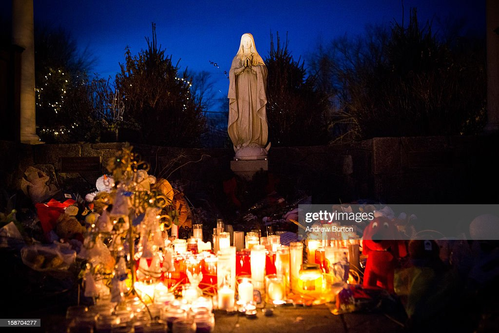 Candles left as a memorial for those killed in the school shooting at Sandy Hook Elementary School sit beneath a statue of the Virgin Mary on December 24, 2012 in Newtown, Connecticut. Donations and letters are pouring in from across the country as the town tries to recover from the massacre.