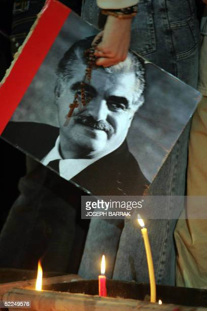 Candles light a portrait of expremier Rafiq Hariri as people gather at his grave in downtown Beirut 27 February 2005 on the eve of rival rallies...