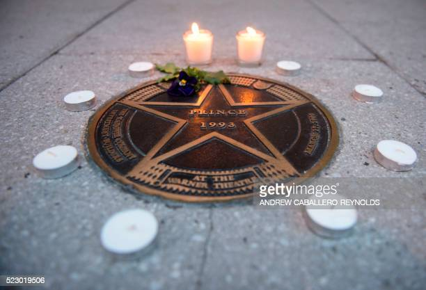 TOPSHOT Candles lit in remembrance to Prince are seen around his star outside the Warner Theatre in Washington DC on April 21 2016 Emergency...