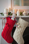 Candles lit on mantelpiece with Christmas stockings