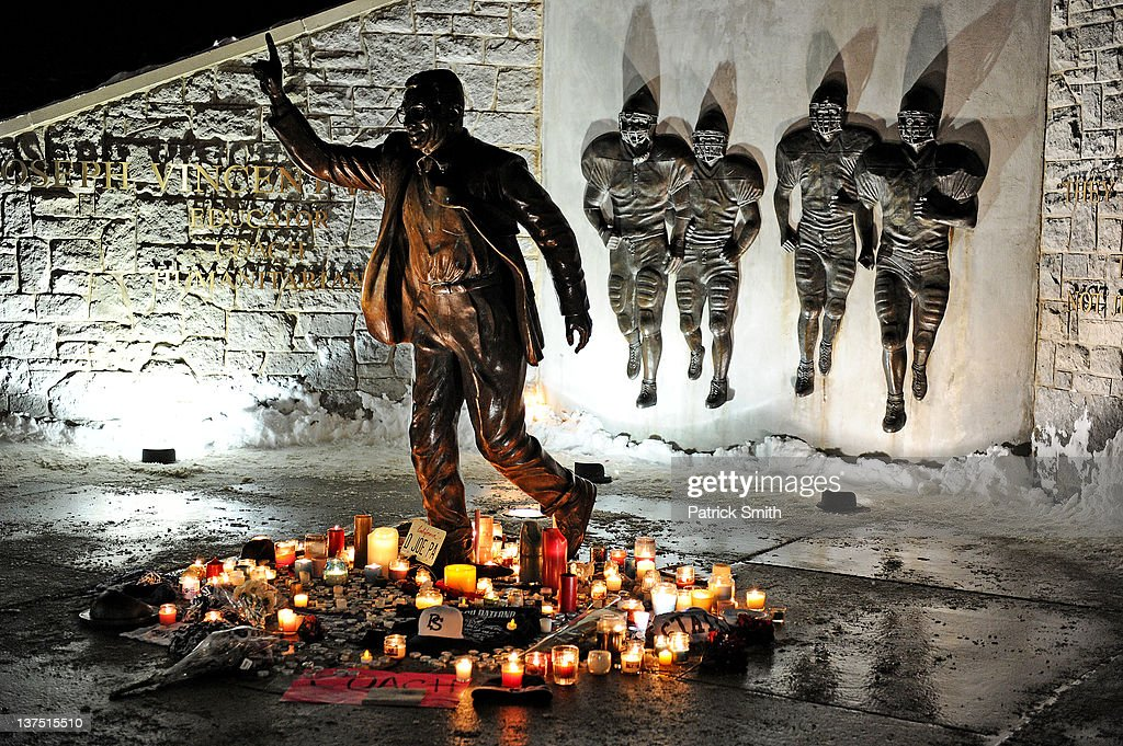 Candles many burnt out circle the statue of Joe Paterno the former Penn State football coach outside of Beaver Stadium in the early hours of January...