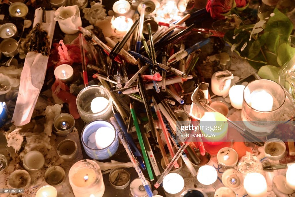 Candles pens and flowers are placed on January 8 on the Place de Republique in Paris during a gathering as a tribute to the 12 people killed by two...