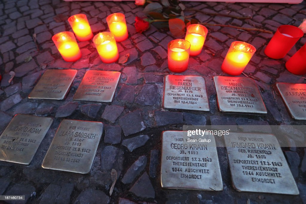 Candles placed at Stolpersteine by local people commemorating the 75th anniversary of the Kristallnacht pogroms cast light on the names of Jewish residents murdered in the Holocaust on November 9, 2013 in Berlin, Germany. Stolpersteine are concrete cobblestones afixed with brass plaques that memorialize local Jewish residents who were murdered or expelled by the Nazis. Events are taking place across Germany today and tomorrow to commemorate the day in 1938 when Nazi gangs across Germany and Austria burned down over 1,000 synagogues, smashed Jewish-owned businesses, looted Jewish residences and killed several hundred Jews. Anti-Semitism was a central component of Adolf Hitler's rise to power and won him wide-spread sympathy among ordinary Germans and Austrians.