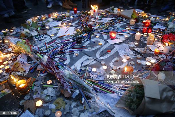 Candles sheets of paper and pens are placed around a graffiti reading 'We are all Charlie' at the Place de Republique in Paris on January 8 a day...