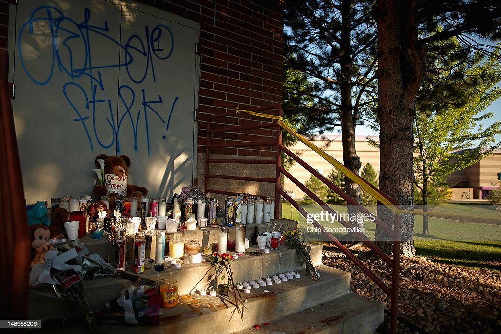 Candles still burn at a makeshift memorial behind the Century 16 movie theater the day after a gunman killed 12 people and injured 59 during an early morning screening of 'The Dark Knight Rises' July 21, 2012 in Aurora, Colorado. Police in Aurora, a suburb of Denver, say they have a suspect James Holmes, 24, in custody.