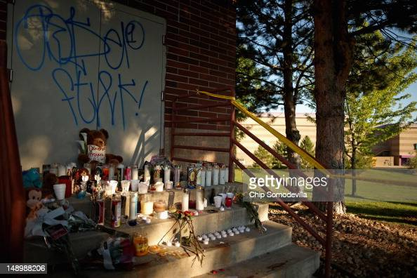 Candles still burn at a makeshift memorial behind the Century 16 movie theater the day after a gunman killed 12 people and injured 59 during an early...