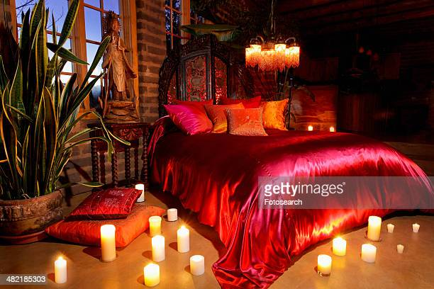 Candles surrounding orange and red bed