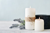 Two candles with lavender flowers on light blue background