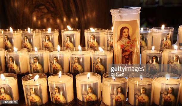 Candles with the face of Saint Therese of Lisieux are lit by pilgrims in Westminster Cathedral at the end of their nationwide tour on October 13 2009...