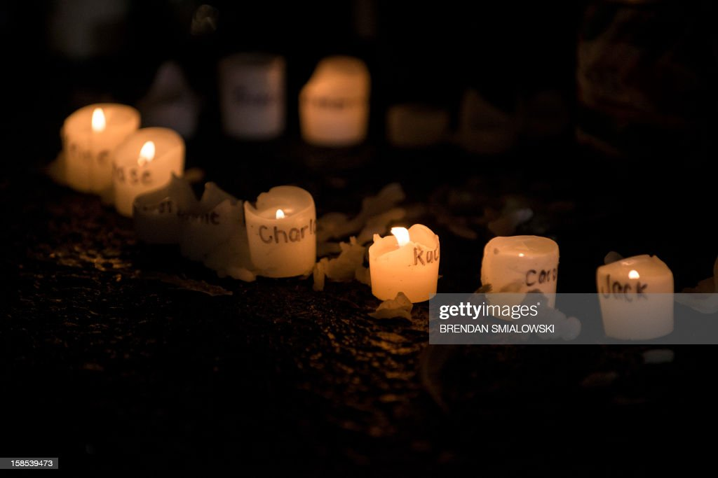 Candles with the names of victims of the Sandy Hook Elementary School shooting written on them are seen at a makeshift memorial near the entrance to the grounds of Sandy Hook Elementary School on December 18, 2012 in Newtown, Connecticut. Students in Newtown, excluding Sandy Hook Elementary School, returned to school for the first time since last Friday's shooting at Sandy Hook which took the live of 20 students and 6 adults. AFP PHOTO/Brendan SMIALOWSKI
