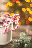 Candy canes in a small white pail on wooden table.