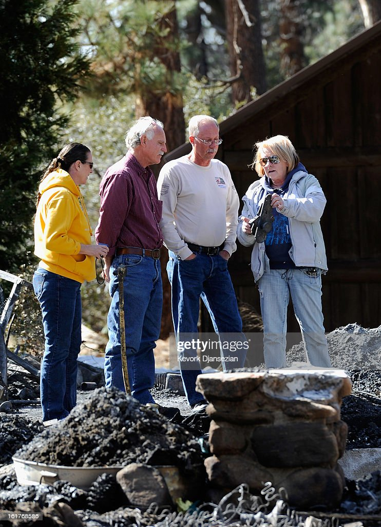 Candy Martin (R) holds a charred door knob as she surveys the damage with family members and friends at her burned-out cabin where the remains of multiple murder suspect and former Los Angeles Police Department officer Christopher Dorner were found on February 15, 2013 in Big Bear, California. Dorner, a Navy Reserve veteran, barricaded himself in the cabin and engaged law enforcement officers in a shootout, killing one and wounding another. Dorner's body was identified after being found in the burned out cabin.