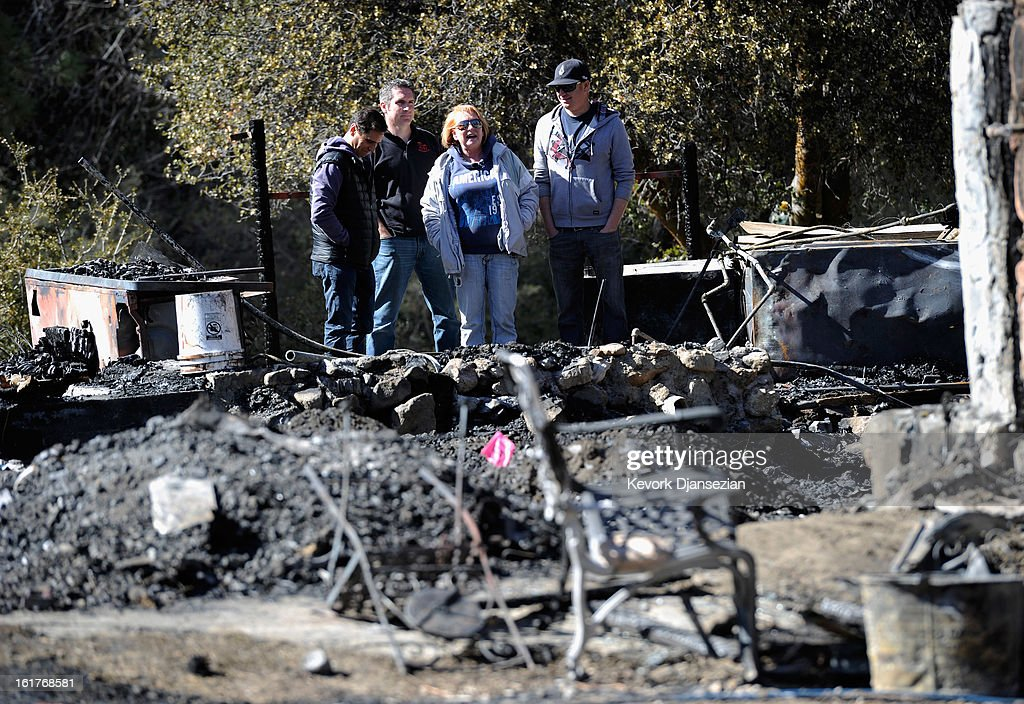 Candy Martin (C) surveys the damage with family members and friends at her burned-out cabin where the remains of multiple murder suspect and former Los Angeles Police Department officer Christopher Dorner were found on February 15, 2013 in Big Bear, California. Dorner, a Navy Reserve veteran, barricaded himself in the cabin and engaged law enforcement officers in a shootout, killing one and wounding another. Dorner's body was identified after being found in the burned out cabin.