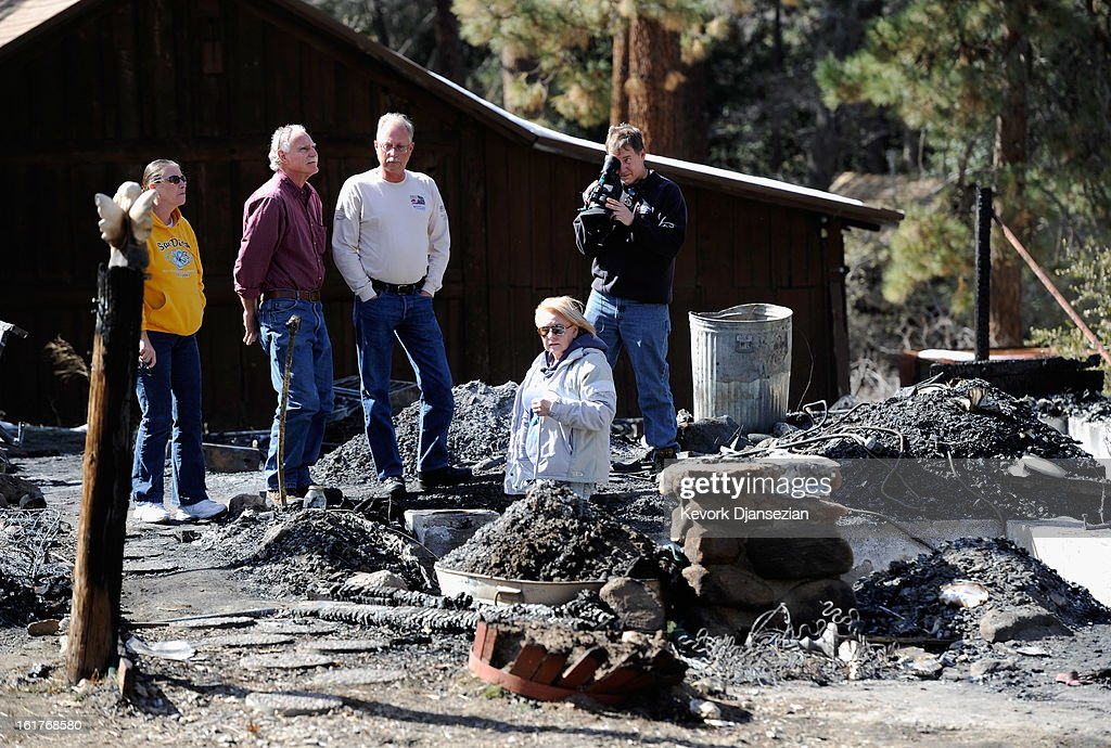 Candy Martin (2nd R) surveys the damage with family members, friends and a television crew member at her burned-out cabin where the remains of multiple murder suspect and former Los Angeles Police Department officer Christopher Dorner were found on February 15, 2013 in Big Bear, California. Dorner, a Navy Reserve veteran, barricaded himself in the cabin and engaged law enforcement officers in a shootout, killing one and wounding another. Dorner's body was identified after being found in the burned out cabin.