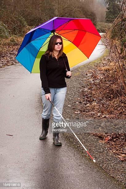 Cane Benutzer mit bunten Regenschirm auf dem Trail
