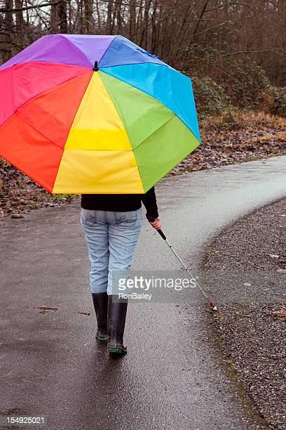 Cane utilisateur avec parasol sur sentier lumineux