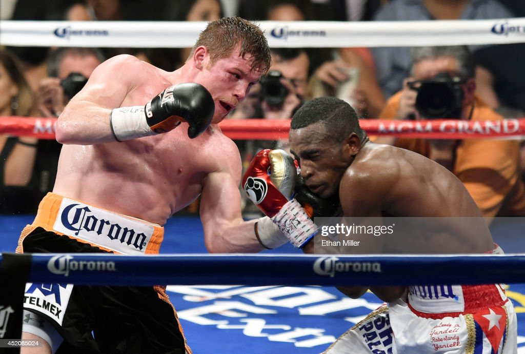 Canelo Alvarez (L) hits Erislandy Lara in the seventh round of their junior middleweight bout at the MGM Grand Garden Arena on July 12, 2014 in Las Vegas, Nevada. Alvarez won in a split decision.