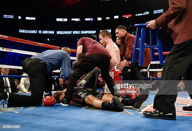 Canelo Alvarez kneels over Amir Khan as officials tend to Khan after Alvarez delivered a knockout punch during the sixth round of their WBC...