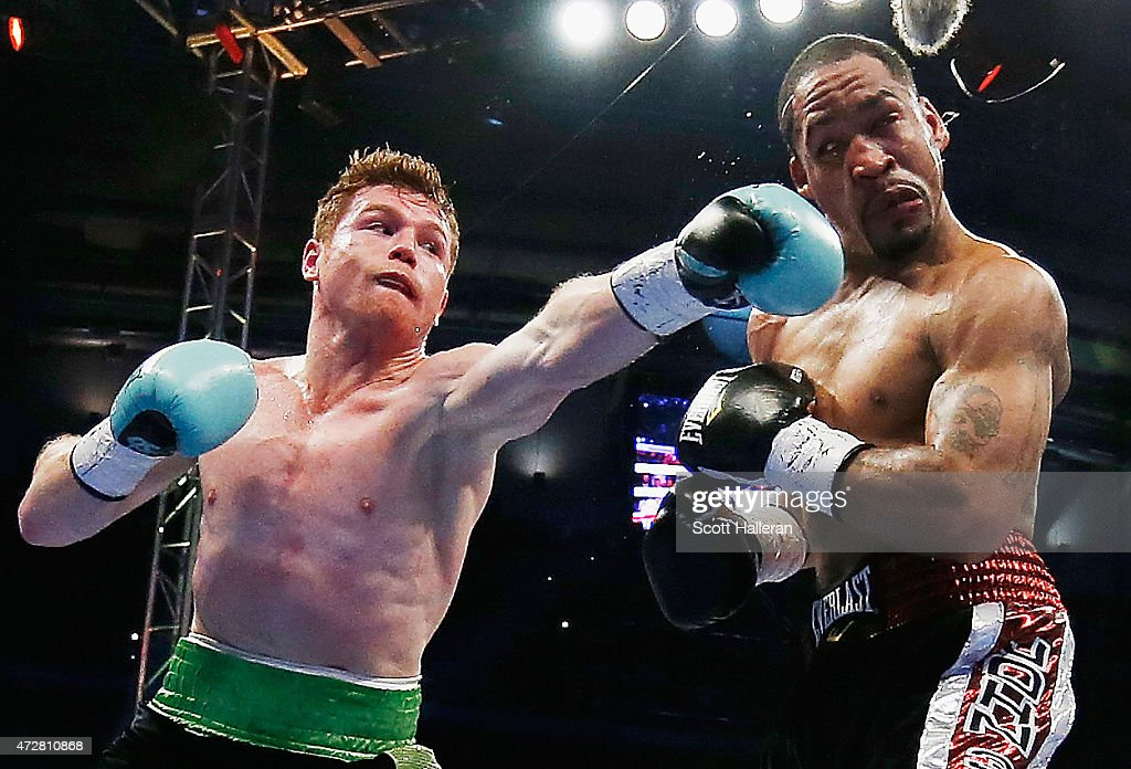 Canelo Alvarez of Mexico (L) delivers a punch to James Kirkland during their super welterweight bout at Minute Maid Park on May 9, 2015 in Houston, Texas.