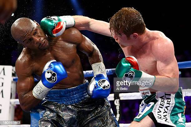 Canelo Alvarez throws a right at Floyd Mayweather Jr during their WBC/WBA 154pound title fight at the MGM Grand Garden Arena on September 14 2013 in...