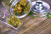 Detail of cannabis buds (scout master strain) on glass jar over wood background - medical marijuana dispensary concept