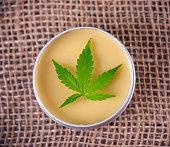 Detail of cannabis hemp cream with marijuana leaf over burlap background - cannabis topicals concept