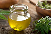 Delicious homemade cannabis oil with marijuana buds and leaf.