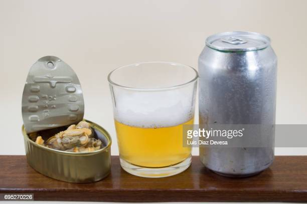 canned clams in clam juice, beer Can and glass of beer
