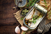 Open tin of sardines in olive oil with capers and thyme on dark rustic wooden background