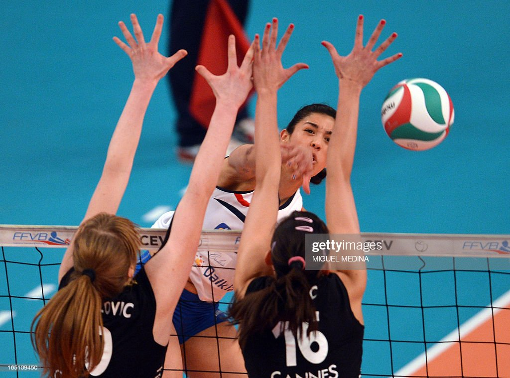 Cannes' Brankica Mihajlovic (L) and Milena Rasic (R) try to block Calais' Maria Jose Perez Gonzalez during their Women French Championship volleyball final match Cannes vs Calais on March 30, 2013 at the Coubertin Stadium in Paris.