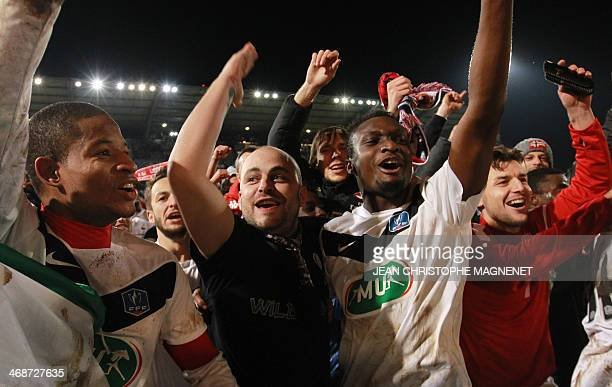 Cannes' Elias Uzamukunda and Cannes' Stephane Marignale celebrate with supporters after the team won the French Cup football match between Cannes and...