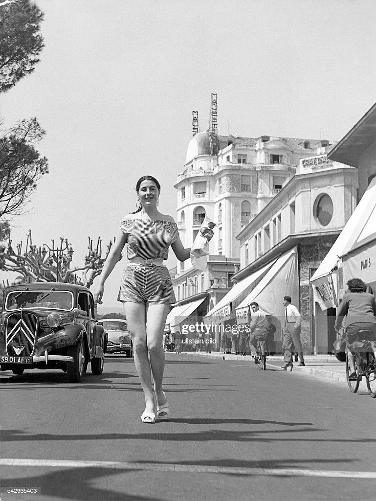 La Croisette in Cannes eine junge Frau läuft die Strasse hinunter ein eingepackte4s Baguette und die Sonnebrille in der Hand um 1959