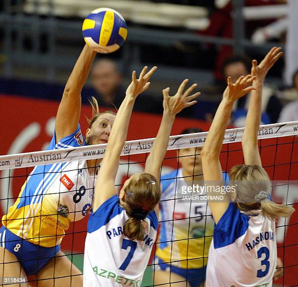 Cannes' German player Olesja Kulakova spikes on the block of Azerrail Baku's Yelena Parkhomenko and Alla Hasanova during their women's volleyball...