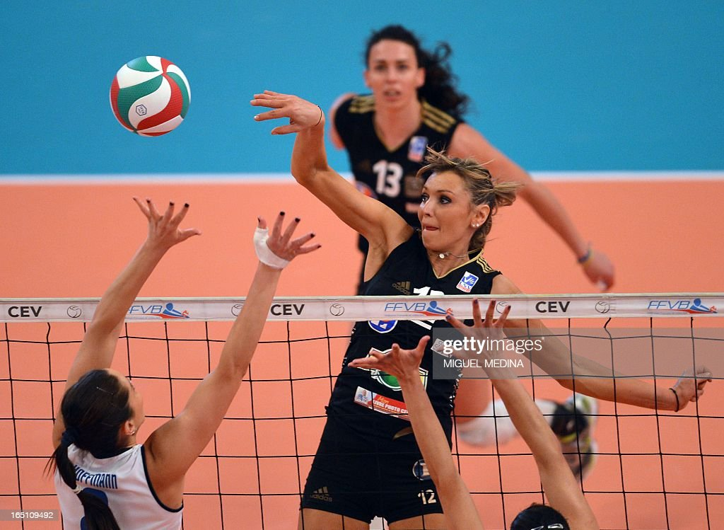 Cannes' Victoria Ravva (C) jumps to spike during the Women French Championship volleyball final match Cannes vs Calais on March 30, 2013 at the Coubertin Stadium in Paris.