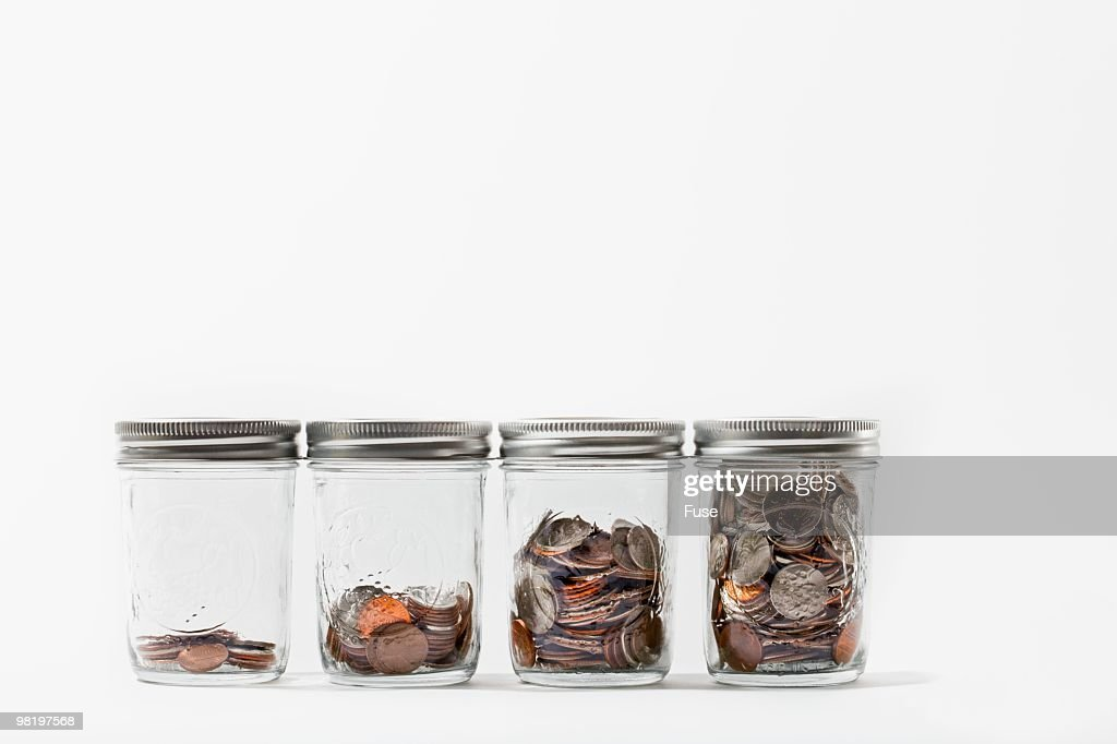 Canning jars containing various amounts of coins