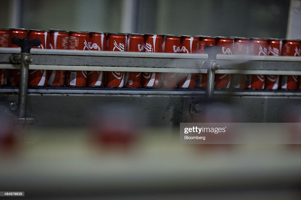 A canning machine fills cans with Coca-Cola Co. beverage at the Habib Gulzar Non-Alcoholic Beverage Ltd. bottling facility in Kabul, Afghanistan, on Thursday, April 10, 2014. Coca-Cola Co., the world's largest soda maker, today showed signs of a rebound in the first three months of the year, easing the concerns that arose when the company unsettled investors with surprisingly sluggish global sales in the fourth quarter. Photographer: Victor J. Blue/Bloomberg via Getty Images