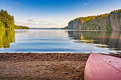 Stock photo of red colored canoe lying on a beach at tranquil Bon Echo Provincial Park in Ontario Canada. Adventure, travel, journey concept.