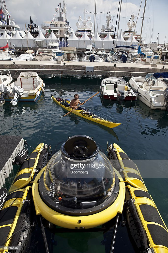 A canoeist paddles past a C-Explorer 2 submarine, manufactured by U-Boat Worx, as it sits moored during the Monaco Yacht Show (MYS) in the harbor in Monaco, France, on Wednesday, Sept. 25, 2013. Over 100 of the world's luxury yachts will be displayed in Port Hercules during the 23rd MYS which runs from Sept. 25 - 28. Photographer: Balint Porneczi/Bloomberg via Getty Images