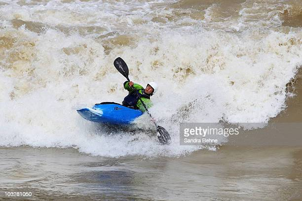 A canoeist rides on the Isar river at Reichenbach bridge on August 7 2010 in Munich Germany The standing wave in Munich forms on the Isar itself near...