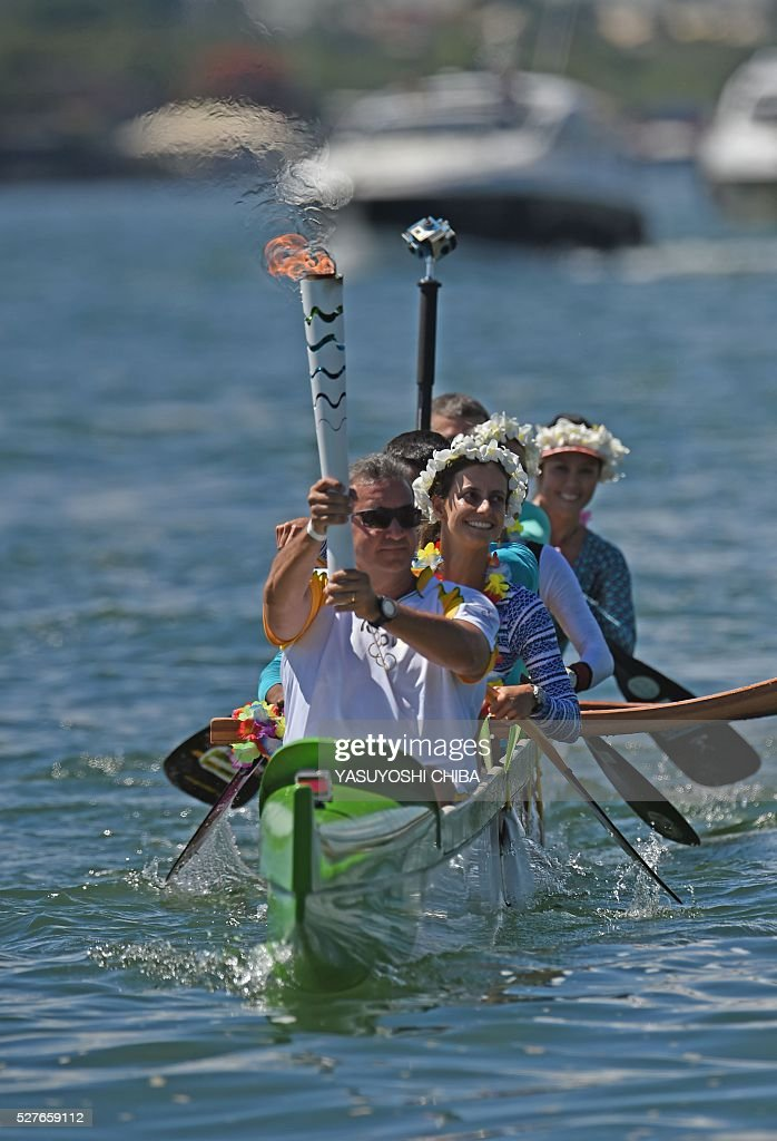 Canoeist Rubens Pompeu carries the Olympic flame on an outrigger canoe at Lake Paranoa in Brasilia on May 3. Embattled President Dilma Rousseff greeted the Olympic flame in Brazil on Tuesday, promising not to allow a raging political crisis, which could see her suspended within days, to spoil the Rio Games. The torch will now be carried in a relay by 12,000 people through 329 cities, ending in Rio's Maracana stadium on August 5 for the opening ceremony. / AFP / YASUYOSHI