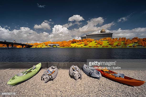 Canoes At Lakeshore Against Sky In City During Autumn