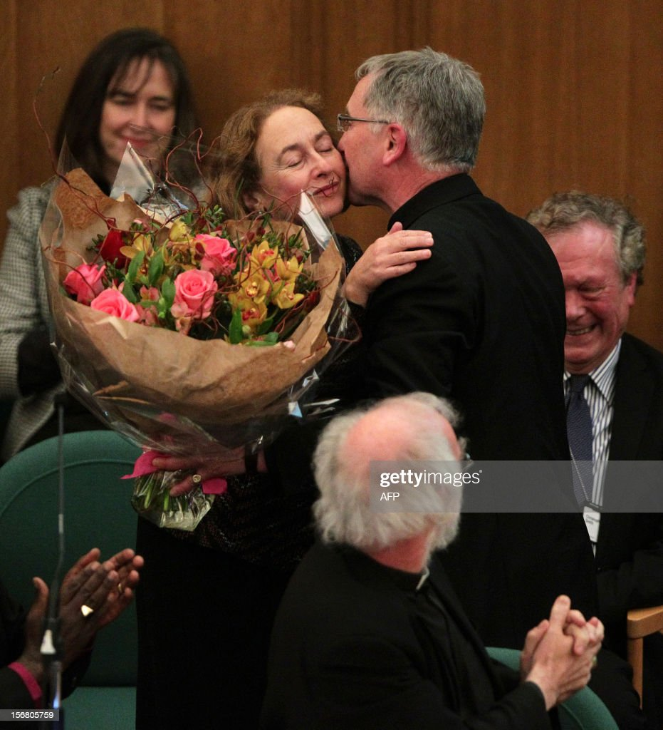 Canon Glyn Webster presents a bouquet of flowers to Jane Williams, the wife of outgoing Archbishop of Canterbury Rowan Williams as they pay tribute to him during a meeting at the General Synod of the Church of England, at Church House in central London on November 21, 2012. The Church of England has 'undoubtedly' lost credibility after voting to reject the appointment of women bishops, its leader the Archbishop of Canterbury said on November 21.