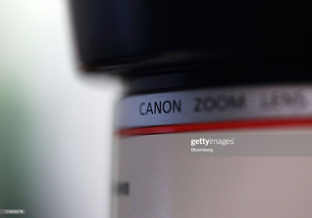 Canon Inc. branding is seen on a lens for the EOS series digital camera in this arranged photograph in Tokyo, Japan, on Tuesday, July 23, 2013. Canon Inc., the world's largest camera maker, is scheduled to release earnings on July 24. Photographer: Tomohiro Ohsumi/Bloomberg via Getty Images